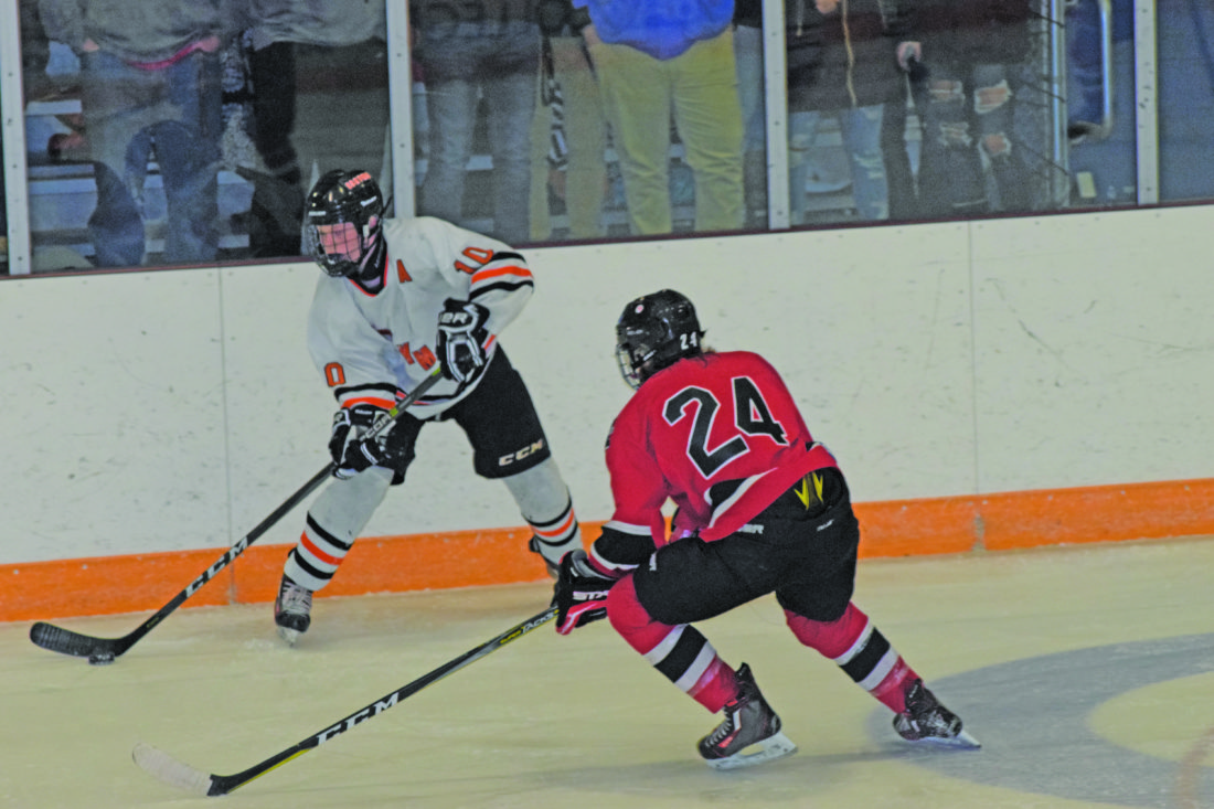Mike Mattson   Daily Press Escanaba's Grant Wickham moves the puck along the boards as Marquette's Sean O'Connor defends in Tuesday night's home opener for the Eskymos.