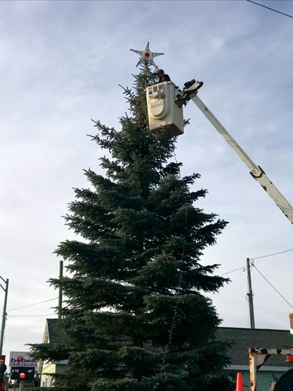 Haley Gustafson | Daily Press   Chris Proehl places a star on top of the Rapid River community Christmas tree on Sunday. The tree, located just off US-2 in Rapid River, was donated by a Rapid River resident. A tree lighting ceremony will take place at 5 p.m. on Saturday after the Christmas in Rapid River event.