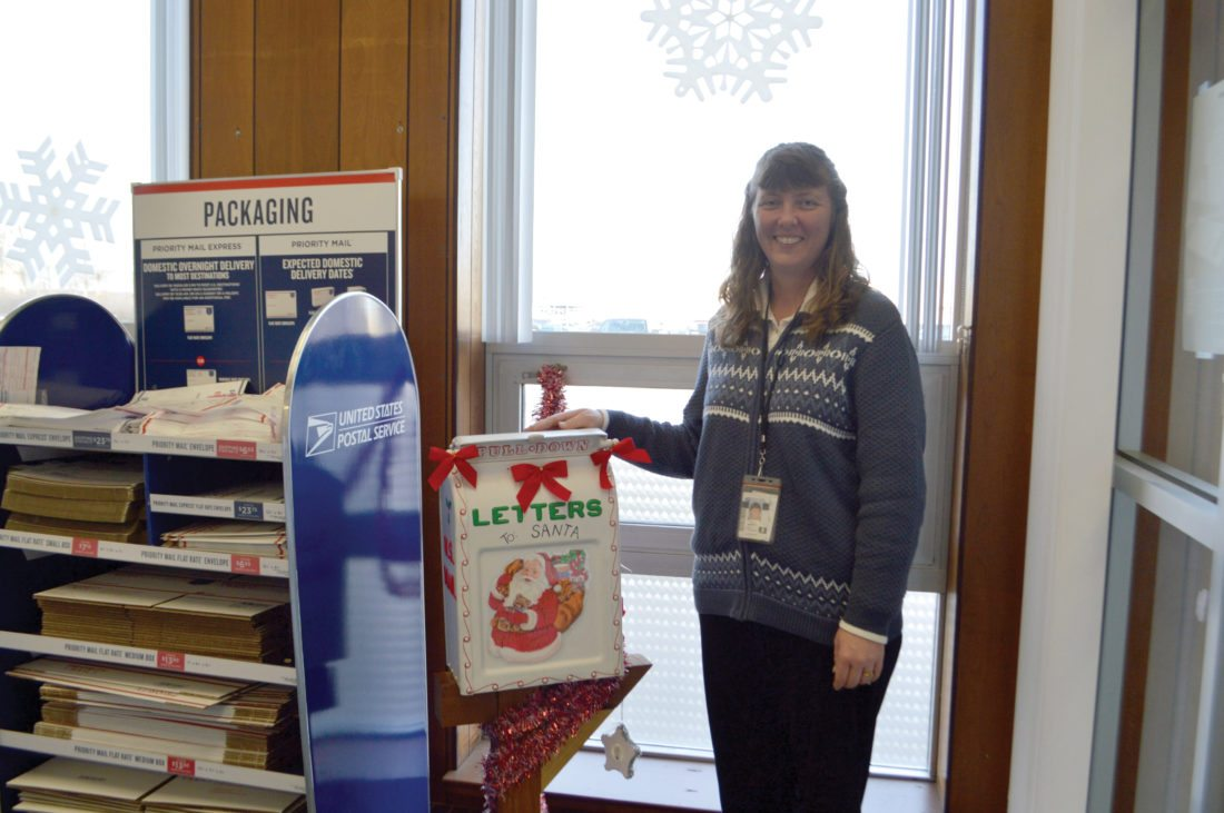 Haley Gustafson | Daily Press Kristine Imhoff, supervisor at the Escanaba United States Postal Service (USPS) office showcases the box that people can mail letters to Santa Claus.