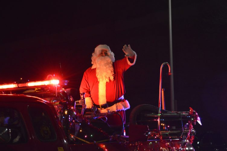 Haley Gustafson | Daily Press Above, Santa Claus waves to the crowd while riding a float during Escanaba's 59th annual Christmas Parade Friday evening on Ludington Street in Escanaba.