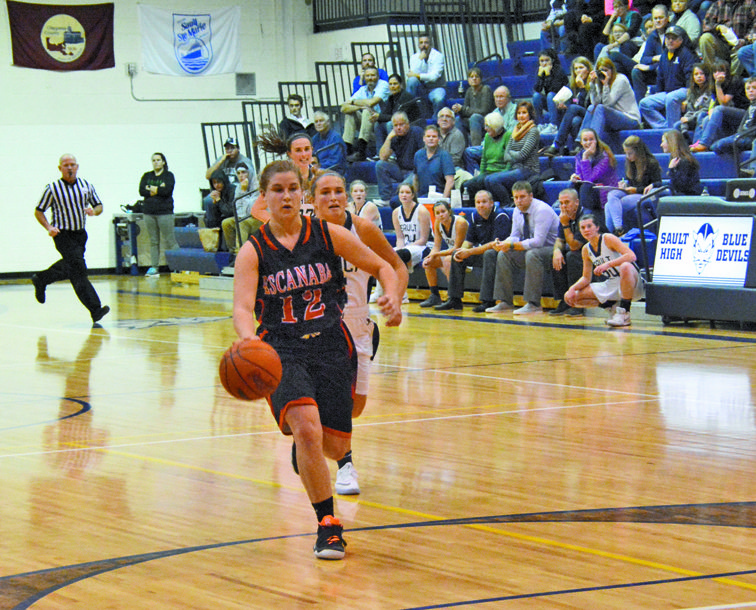 Rob Roos/Sault News Escanaba's Lexi Challier leads a fast break, while Sault High's Mackenzie Kalchik chases the play during a non-conference girls basketball game Saturday. The Eskymos spilled the Blue Devils 38-37.