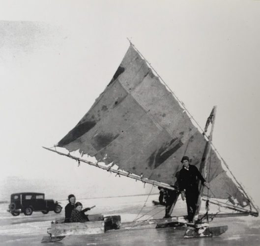 """Courtesy photo From left, Ray Hansen and his sons Allen and Jim, along with Hoppi Cass, sit in an ice boat off the frozen lake shore across from the present day Escanaba Athletic Field in the winter of 1955. Jim, a retired Escanaba High School principal, still ice boats today on the DN Ice Boat he built in 1978. Ray Hansen was a commercial fisherman and was instilled the passion for sailing at a young age. Jim has continued to be enthused about sailing both on the ice and on all over the Great Lakes on his sailboat the """"Gallivant."""" Each summer, Jim and his first mate, Alice, offer sailboat adventure tours for parties of six with all donations going to Lakestate Industries and other organizations."""