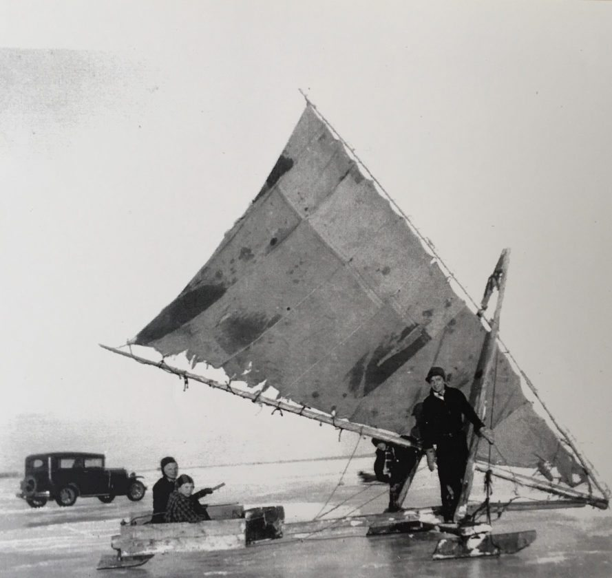 "Courtesy photo From left, Ray Hansen and his sons Allen and Jim, along with Hoppi Cass, sit in an ice boat off the frozen lake shore across from the present day Escanaba Athletic Field in the winter of 1955. Jim, a retired Escanaba High School principal, still ice boats today on the DN Ice Boat he built in 1978. Ray Hansen was a commercial fisherman and was instilled the passion for sailing at a young age. Jim has continued to be enthused about sailing both on the ice and on all over the Great Lakes on his sailboat the ""Gallivant."" Each summer, Jim and his first mate, Alice, offer sailboat adventure tours for parties of six with all donations going to Lakestate Industries and other organizations."