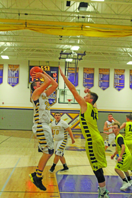Avery Bundgaard | Daily Press Rapid River's Logan Hardwick (22) puts up a shot over Carney-Nadeau's Jordan Janofski (44) Monday during the first half in Rapid River.