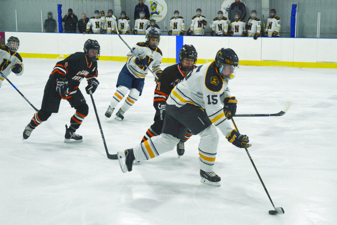 Journal photo by Corey Kelly Negaunee's Bryce Jarvi moves the puck as  Escanaba's Brayden Stannard defends in Monday's game at the Negaunee Ice Arena.