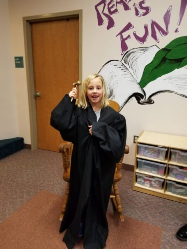 Courtesy photos Above, Hayley Coon, an Escanaba Public Library Storyhour participant, poses for a picture wearing former Delta County Circuit Court Judge Stephen Davis' robe and holding a gavel during a Saturday storyhour at the library. During Davis' time at the library, he explained to the kids what a judge is, what he does, and read two stories. He also discussed about honesty, always telling the truth, bullying and always being kind.