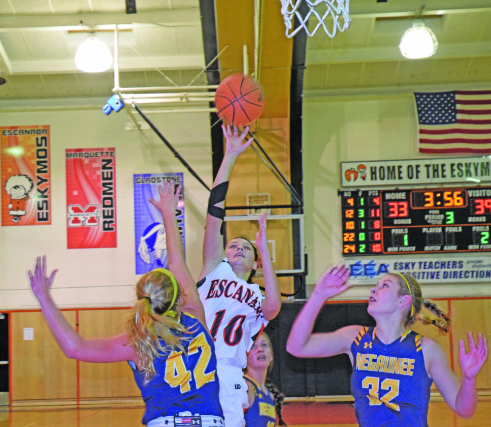 Mike Mattson   Daily Press Escanaba's Mykenzie Monkevich (10) puts up a shot over Negaunee's Abby Nelson (42) in Tuesday night's game.