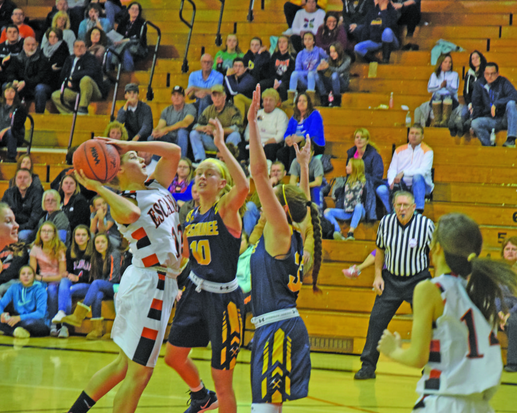 Mike Mattson   Daily Press Escanaba's Lexi Chaillier launches a shot in front of Negaunee's Clara Johnson (10) and Natalie Bartle (33) in Tuesday night's game.