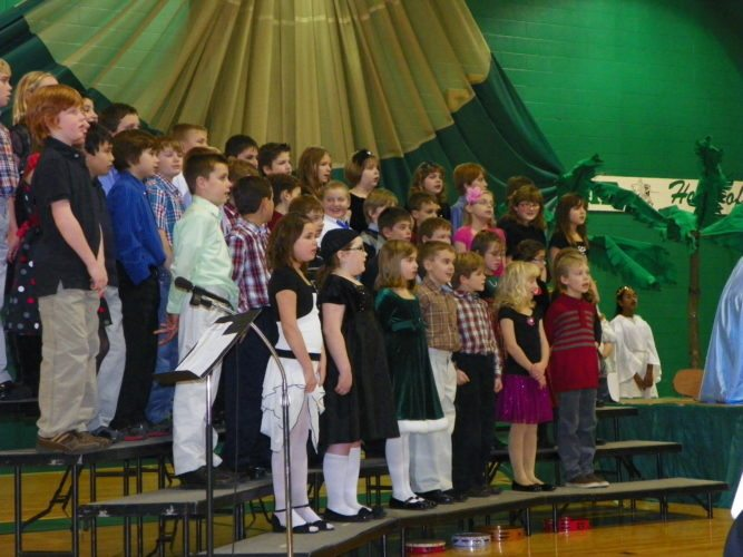 Karen Wils photo On the risers, a class from years ago at Holy Name sings in the Christmas program.