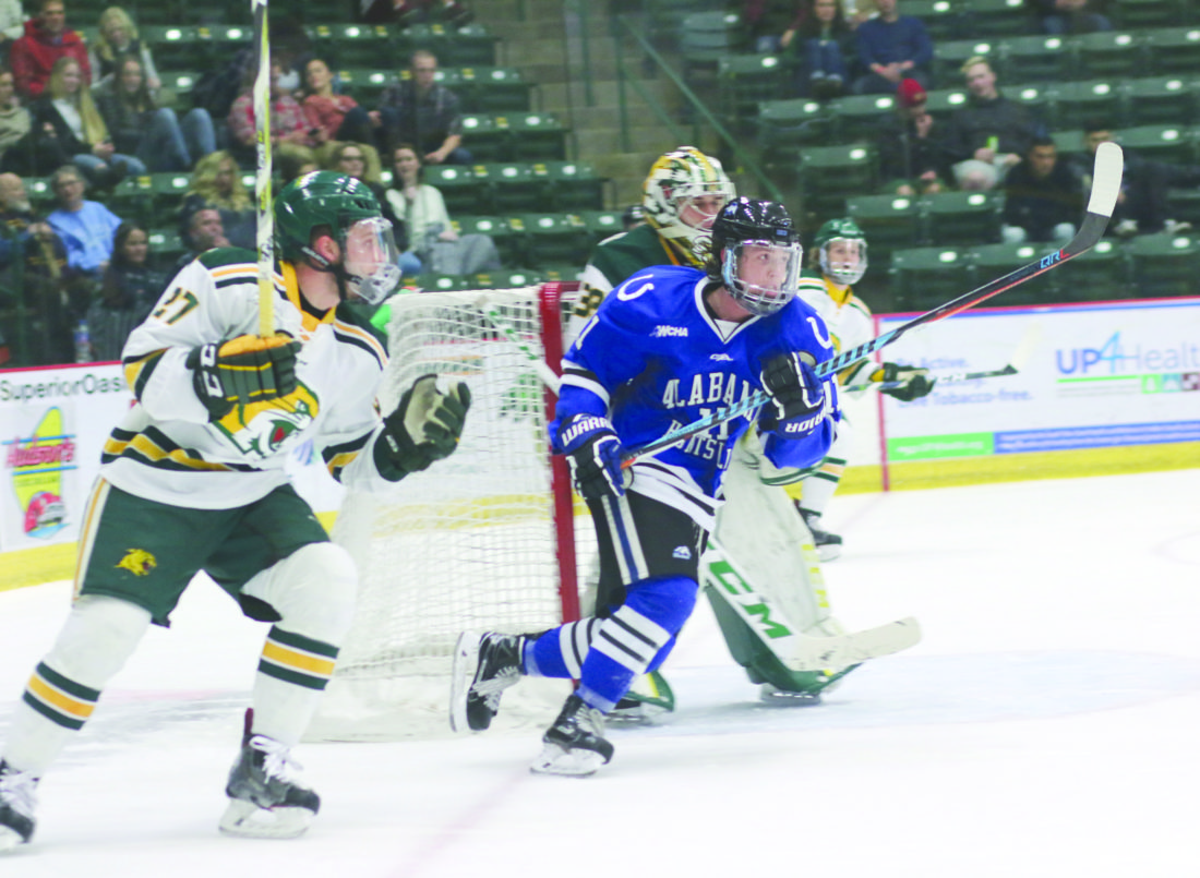 Rachel Oakley | Mining Journal Alabama-Huntsville's Levi Wunder chases after the puck in Northern Michigan's zone, pursued by NMU's Adam Roeder Friday night at the Superior Dome in Marquette.