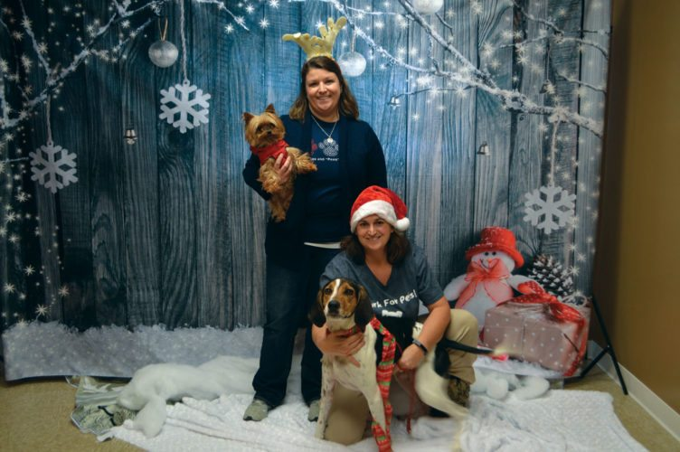 "Haley Gustafson | Daily Press  From left, Tonya Gartland, special events coordinator for the Delta Animal Shelter poses for a picture in a wintery back drop with shelter dog ""Sophie,"" along with Shelter Manager Sue Gartland with adoptable shelter dog ""Spark,"" at the shelter in Escanaba Wednesday. The Delta Animal Shelter will be hosting a Christmas open house Saturday from 11 a.m. to 3 p.m. where pets can have their pictures taken with Santa Claus along with other activities."