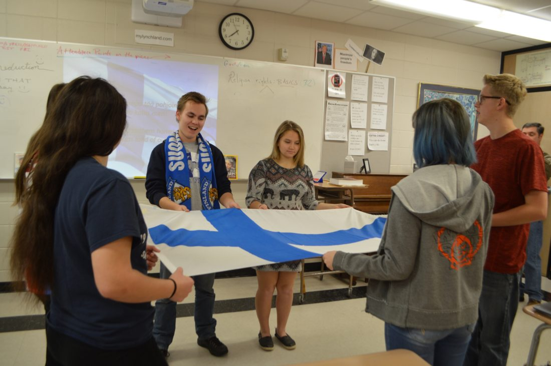 Haley Gustafson | Daily Press  Finnish exchange student Lari Nuutinen, center, sings Finland's national anthem while holding Finland's flag with his Escanaba High School classmates Wednesday during a celebration held for Finland's 100th anniversary of being an independent country. Students participating around the flag, from left, are Escanaba juniors Jenna Pease, Cassandra Kreneck (hidden), Nuutinen, Heather Bergstrom, Brendan Bennett, and Fiona Lindberg.