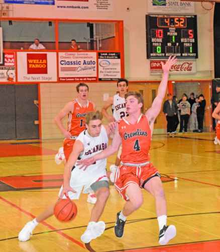 Mike Mattson | Daily Press Escanaba point guard Ryan Robinette (4) races to the basket against Houghton's George Butvilas (4) on a fast break in Tuesday night's game.
