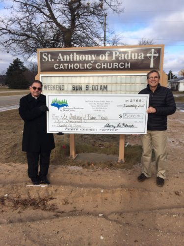 "Courtesy photo At right, Father Rick Courier of St. Anthony of Padua Catholic Church in Wells accepts the $5,000 check from Community Foundation for Delta County Board Chair Charles Becker for the church's ""Elevator Car"" project."