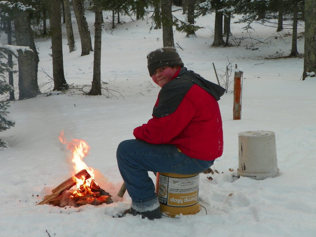 Karen Wils photo Bob makes a campfire to stay warm in the wintry outdoors.