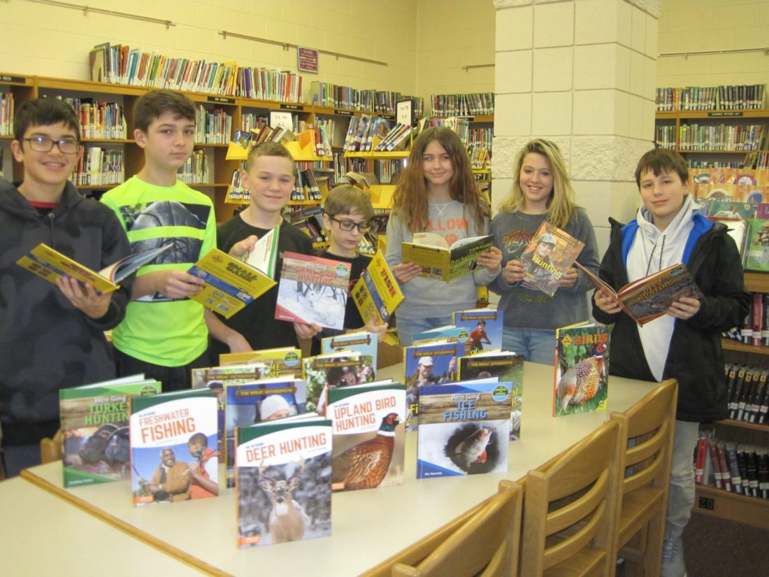 Courtesy photo The Gladstone School and Public Library recently received a donation from the U.P. Whitetails Association. The funds were used to purchase four complete collections of nonfiction books for young adults, who enjoy wildlife and the outdoors.  Above, seventh grade hunting enthusiasts, from left, John Bichler, Noah Peterson, Braden Sundquist, Eli Terrien, Tansy Beauvais, Abby Johnson and John Roman were excited to check out the new books.