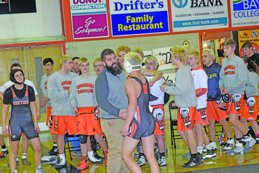 Mike Mattson | Daily Press Escanaba coach Jeff Wright congratulates Tyler Lawson after his 5-4 win in the 130-pound bout Tuesday night.