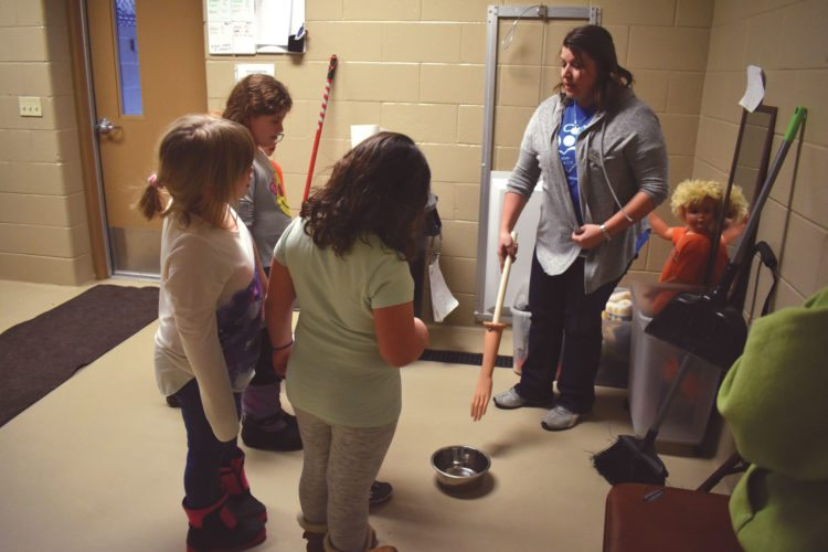 Haley Gustafson | Daily Press  At far right, Tonya Gartland, special events coordinator for the Delta Animal Shelter in Escanaba, discusses how shelter personnel test a dog for signs of food aggression (when a hand reaches for the dog's food bowl) Tuesday evening during the shelter's first session of Kids P.A.C.K. The educational program, aimed at helping and teaching kids how to properly take care of animals, will host sessions on the first and second Tuesdays of each month from 4:30 to 6 p.m. at the shelter.