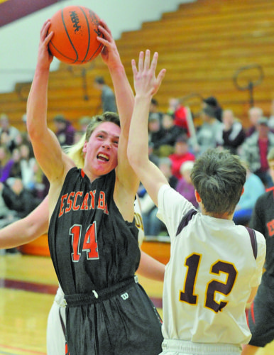 EagleHerald/Stephen Oman Escanaba's Craig Kamin goes up for a shot against Menominee Monday at Menominee High School.