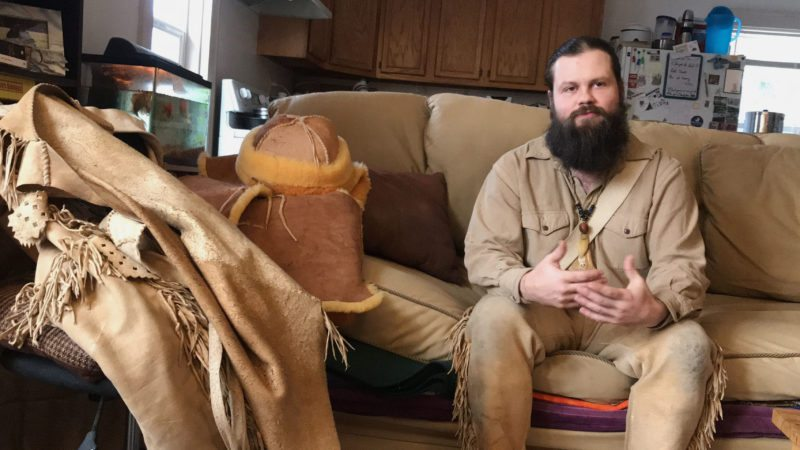 In this undated photo, Sean Sullivan sits in his Wausau, Wis., apartment with some of the clothes he has made from hides, most of which he tanned himself. Sullivan's choice of fashion is distinctly frontier fur-trader style, with his homemade buck-skin fringed shirts, elk-skin pants, moccasins and dark beard reaching down to his chest. (Keith Uhlig/The Wausau Daily Herald via AP)