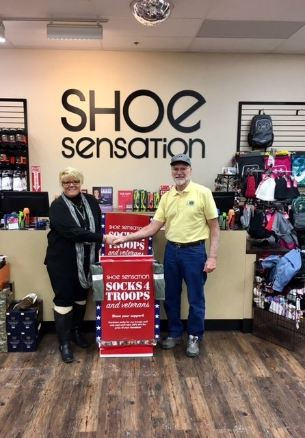 Courtesy photo Shoe Sensation Store Manager Marge Derkos shakes hands with Jeff Ware of the Days River Lion's Club. The Lions will help distribute the socks collected through Shoe Sensation's Socks for Troops program.