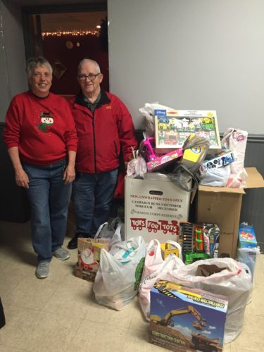 Courtesy photo The Escanaba Eagles Auxiliary recently held their annual Christmas party and asked attendees to bring toys to donate to the United States Marines Toys for Tots Drive.  The box was over- flowing.  Shown in the photo at left are Nancy Gage, left, representing the Eagles Auxiliary and Bill LaMarch, representing Toys For Tots. The Eagles have been donating to Toys for Tots for many years, as well as many other local not-for-profits.