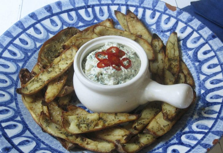 "This Jan. 9 photo shows potato skins baked with roasted garlic rosemary butter and an onion kale dip spiked with fresh chiles. This dish is from the recipe ""Decadent Snacks for the Super Bowl"" by Sara Moulton. (Sara Moulton via AP)"