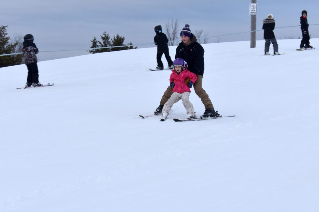 Haley Gustafson | Daily Press  Escanaba High School junior Dan Martin, in back, helps Rapid River kindergartner, Edye, make her way down the ski hill at the John and Melissa Besse Sports Park in Gladstone Thursday during the park's after school program.