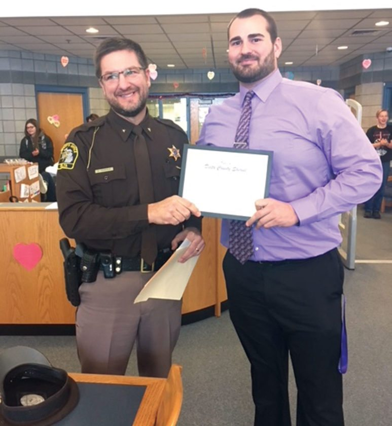 Courtesy photo Delta County Sheriff Ed Oswald, left, presents Gladstone Area High School U.S. history teacher and football/track coach Kent King with a lifesaving award for his actions at the scene of a rollover accident that happened last fall.