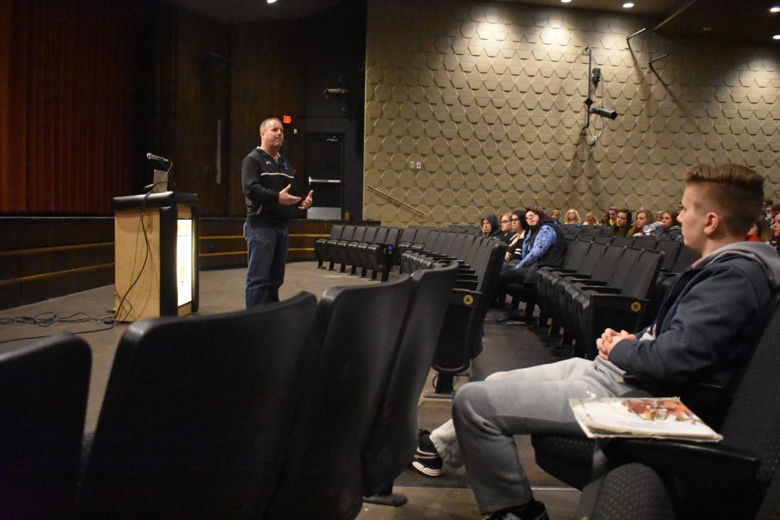 "Haley Gustafson | Daily Press  Jeff Olson, left, speaks to a group of Escanaba High students in the school's auditorium Thursday during a presentation for his suicide awareness program ""Do it For Daniel.""  Olson, who is a high school teacher, father, and football coach at Ishpeming High School in Ishpeming, lost his son Daniel, to suicide in 2012 and now travels the state to raise awareness of suicide prevention."