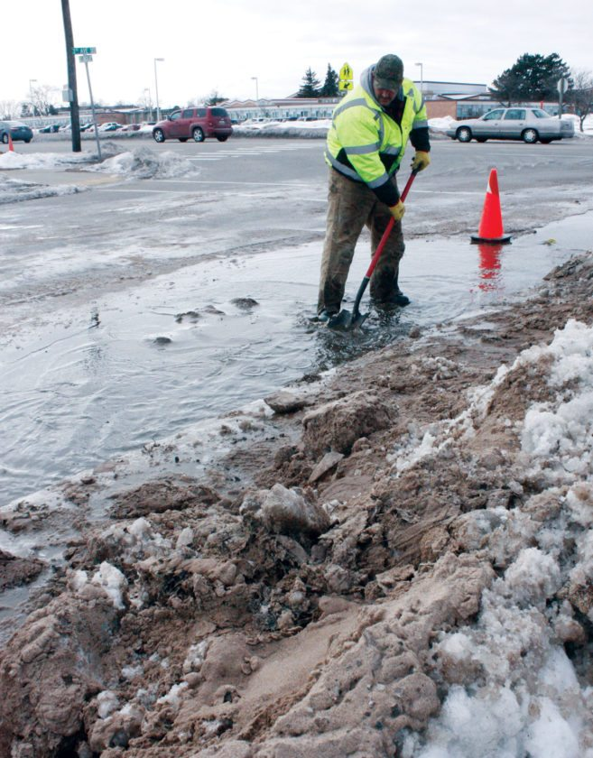 Jenny Lancour | Daily Press Escanaba Water Department employee Jody Welch clears sand at a water main break Monday on South Lincoln Road. The broken water line is being repaired today.