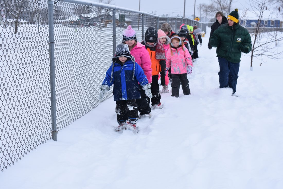 Haley Gustafson | Daily Press  In front, Colton Campfield, a Webster Elementary School first grader, leads his fellow classmates around the school's playground during a snow shoeing activity Wednesday in Escanaba. Debbie O'Connell, right, a physical education teacher at Webster, said snow shoeing is a great way to stay active in the winter months. She hopes by teaching the students how to snowshoe, they will continue the practice.