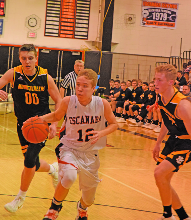 Mike Mattson | Daily Press Escanaba's Peyton Fedell (12) drives past Iron Mountain's Foster Wonders (00) toward the basket in Tuesday's game.