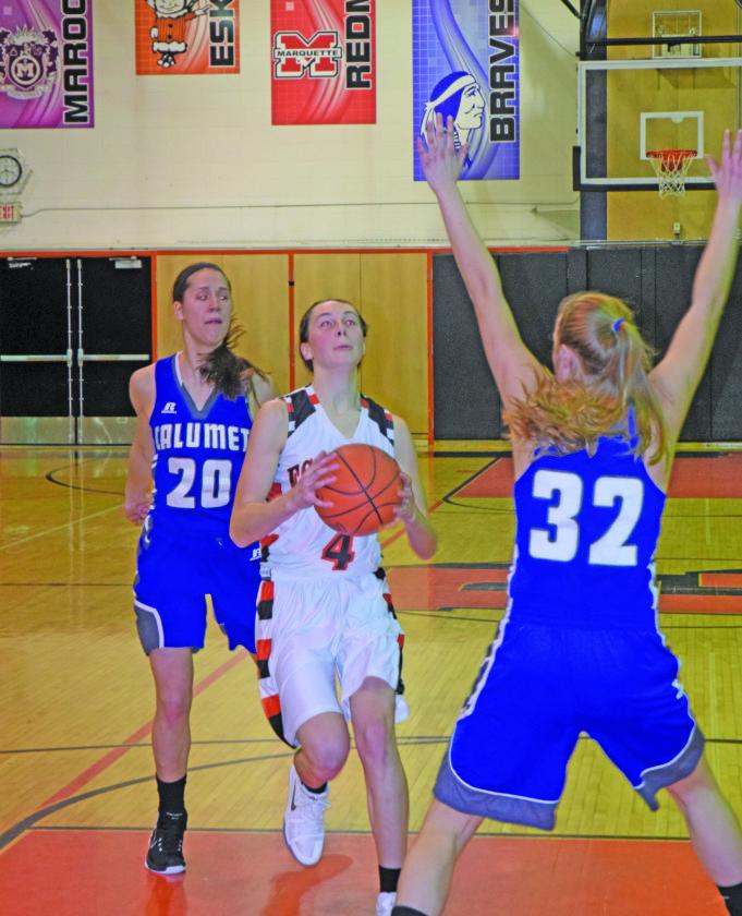 Mike Mattson | Daily Press Escanaba's Nicole Kamin (4) attacks the basket between Calumet defenders Lea Bjorn (20) and Brooke Kariniemi.