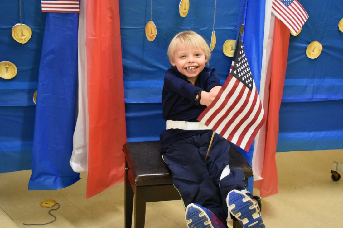 Haley Gustafson | Daily Press  Learning Center student Ethan Witchell is all smiles as he sits in the Olympic theme photo booth at the Delta Schoolcraft Intermediate School District's Learning Center in Escanaba Friday afternoon. The center held its annual winter dance Friday afternoon with an Olympic theme, as the 2018 Olympic winter games kicked-off Friday. Musical entertainment was provided by local band, the Jam Band, along with Olympic-themed snacks and other activities.