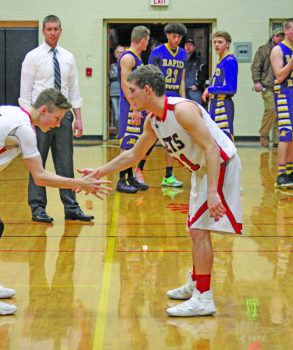 Avery Bundgaard | Daily Press  North Central's Lucas Dombrowski, right, performs a special hand-shake with teammate Griffin Johnson during team introductions Wednesday against Rapid River.