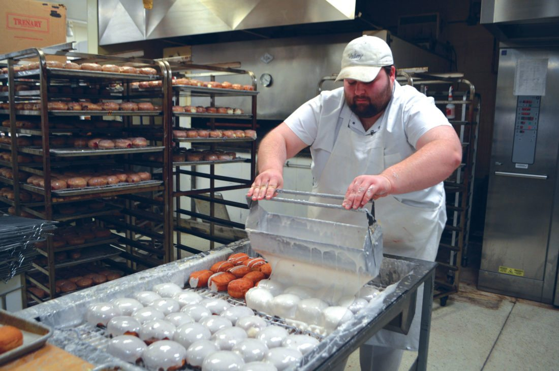 Jordan Beck | Daily Press Gavin Keener, a baker at Elmer's County Market, glazes a tray of paczki at Elmer's Monday. These pastries have become an important part of Fat Tuesday for many people and businesses in the area.