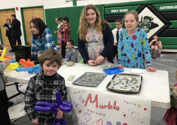 Courtesy photo Nohlyn Kobasic, a preschooler at HNCS, purchases a homemade marble magnet at Holy Name's Entrepreneur Day 2018. The marble magnets were made and sold by HNCS fifth graders, two of which are pictured: Mary Hook and Libby Spreitzer.