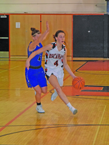 Mike Mattson | Daily Press Escanaba's Nicole Kamin (4) dribbles around Ishpeming's Katie Loman in Thursday night's game. Kamin led the Eskymos with 19 points.