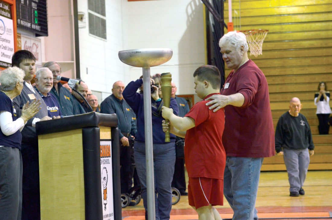 Ilsa Matthes | Daily Press Hunter Hammersmith, representative of Area 1 (Delta, Menominee and Schoolcraft counties) pauses for a moment before lighting the flame to kick off the 41st Annual U.P. Regional Special Olympics Basketball Tournament Friday evening in the Escanaba Area High School gymnasium. Accompanying Hammersmith as he carried the torch was George Dunlap, Area 1 assistant director. The tournament, sponsored by the Escanaba Noon Kiwanis for 41 years, includes more than 350 athletes, volunteer coaches and chaperones.