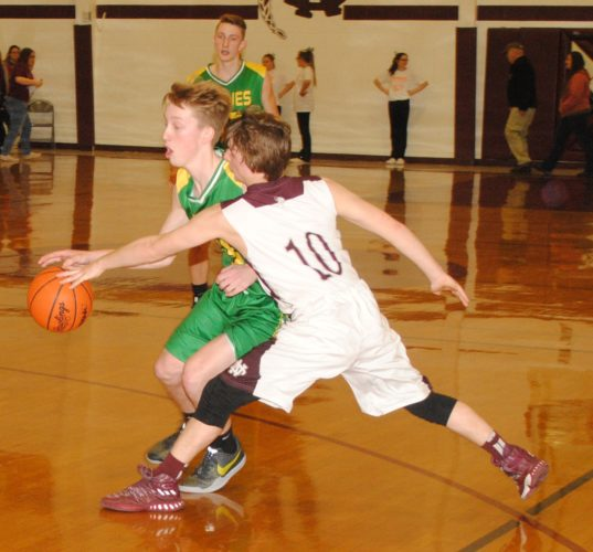 Burt Angeli/The Daily News Photo North Dickinson's Gabriel Johnson (10) defends Carney-Nadeau's Jacob Kleiman (15) in Friday's Skyline Central Conference game at Carl F. Lemin Gymnasium.