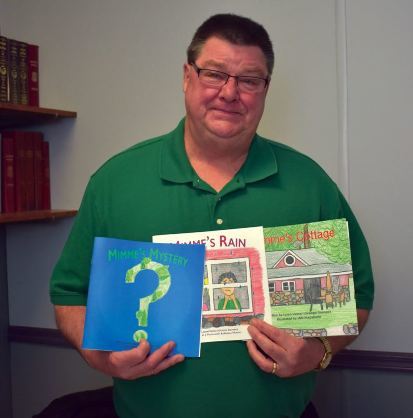 "Haley Gustafson | Daily Press  Loren Veeser, a former Escanaba schools educator and author, displays the children's books he wrote recently. The books in the  three-part series are titled ""Mimme's Cottage,"" ""Mimme's Rain,"" and ""Mimme's Mystery."""