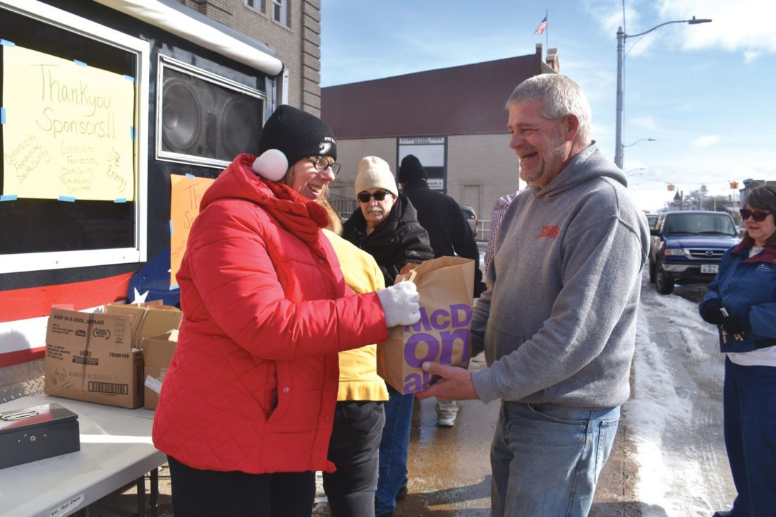 Haley Gustafson | Daily Press  Geri Nelson, left, of DTE Energy, hands off a bag of brats to Wayne Pepin of Escanaba during the Menominee Delta Schoolcraft Community Action Agency's Big Brat Sale Wednesday afternoon in Escanaba.