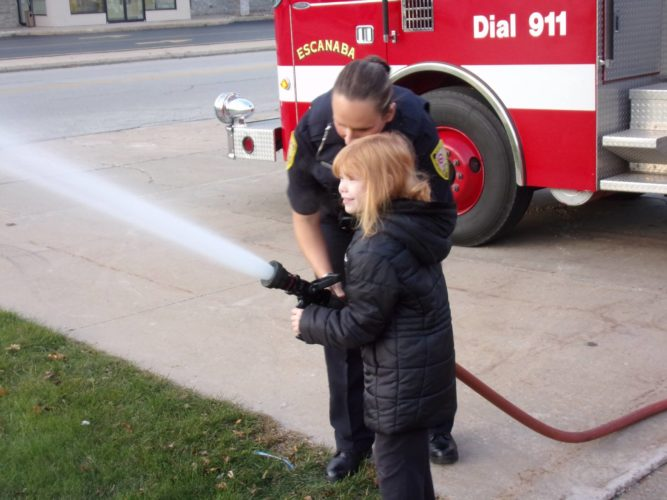 Courtesy photo Escanaba Public Safety Officer Tabitha Marchese, back, helps local school student, Zoey Kramer, shoot the Escanaba Public Safety Department fire truck's hose during Kramer's Hero Program experience. The program, which promotes students in area schools to perform random acts of kindness, has been a huge success since it began in 2016.