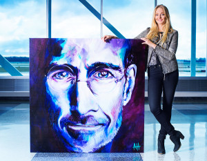 Alex Hall stands with her portrait of the late Apple founder Steve Jobs on display at the Fort Wayne International Airport. Photography by Neal Bruns
