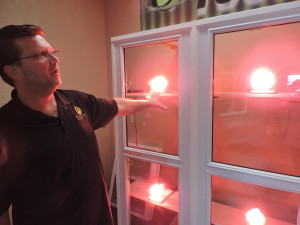 FORT WAYNE NEWSPAPERS Ken Richards of Hoosier Windows and Siding uses a light test to show how heat escapes more readily from certain windows compared to others.