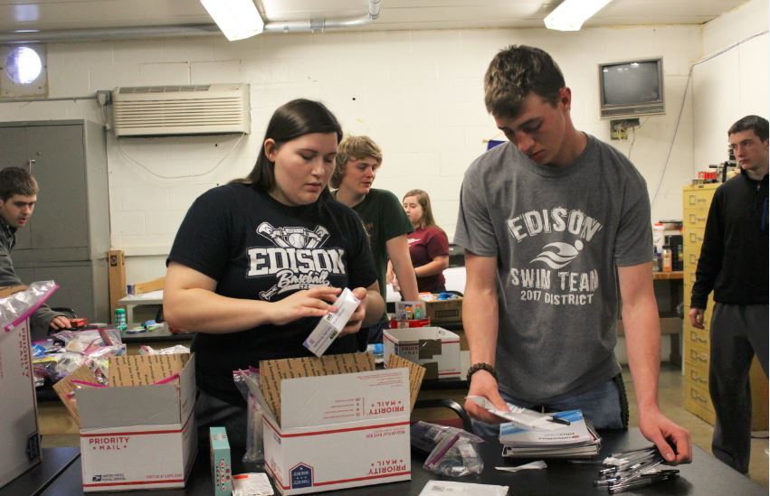 SUPPLIESFOROVERSEAS — Edison High School juniors Sydni Ward, left, and Kyle Koehnlein were among FFA members filling boxes with supplies bound for military service personnel deployed overseas. The organization gathered snacks, hygiene items and miscellaneous goods and filled six boxes, but more care packages likely will be sent due to the large amount of donations. - Contributed