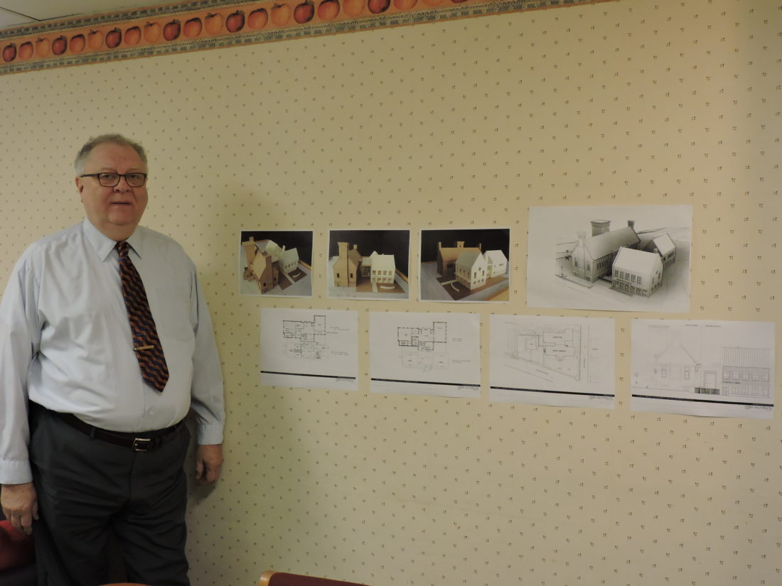 A GLIMPSE OF THE FUTURE — Alan Hall, director of the Public Library of Steubenville and Jefferson County, stands in the library staff lunchroom where copies of the deign plans for the new addition to the main library on South Fourth Street have been placed on the wall. - Dave Gossett