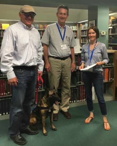 LIBRARYVISITOR — State Sen. Frank Hoagland, left, accompanied by his service dog Stella, recently visited with Assistant Library Director Mike Gray and Genealogist Librarian Erika Grubbs at the Schiappa Branch of the Public Library of Steubenville and Jefferson County. Hoagland had scheduled the library as a local office site to speak to area residents. Grubbs researched Hoagland's family history and shared the information with him during his library visit. -- Contributed