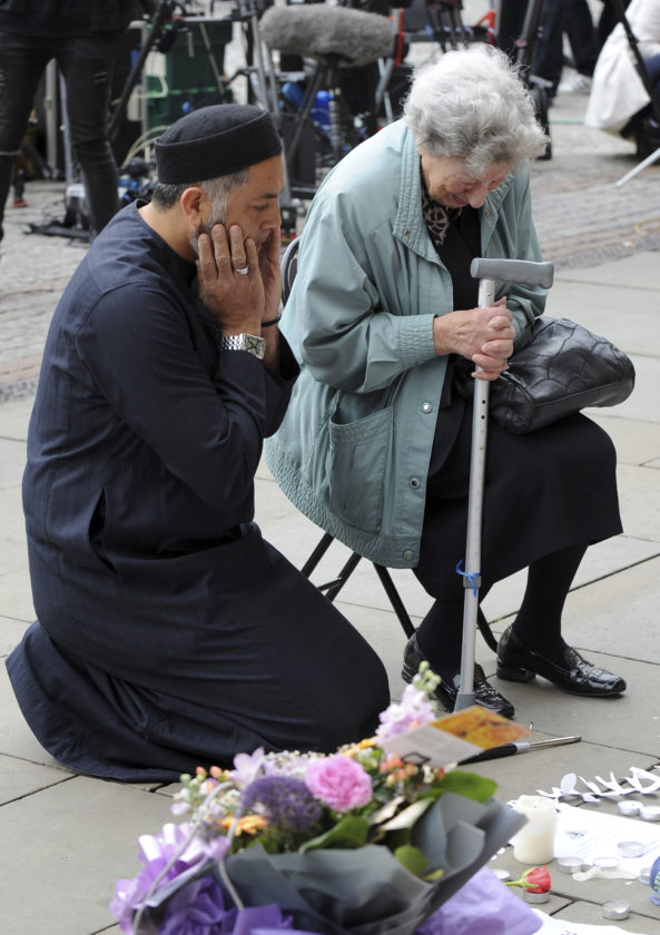 Renee Rachel Black, right, and Sadiq Patelin pray in front of flower tributes at Albert Square central Manchester, England Wednesday May 24 2017. Police confirmed that more than 20 people were killed in an explosion following a Ariana Grande concert at the  Manchester Arena late Monday evening. Britons will find armed troops at vital locations Wednesday after the official threat level was raised to its highest point.